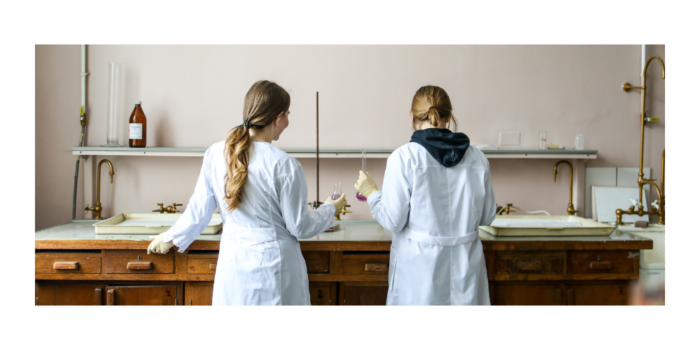 two young women in lab coats standing over lab bench in science class