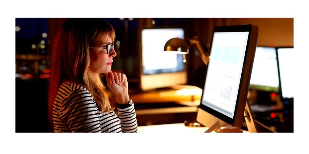 redheaded woman sitting at computer late at night