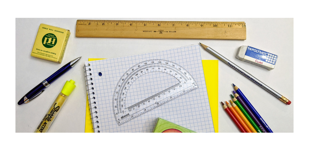 protractor, ruler, pens, pencils and other school supplies on a desk