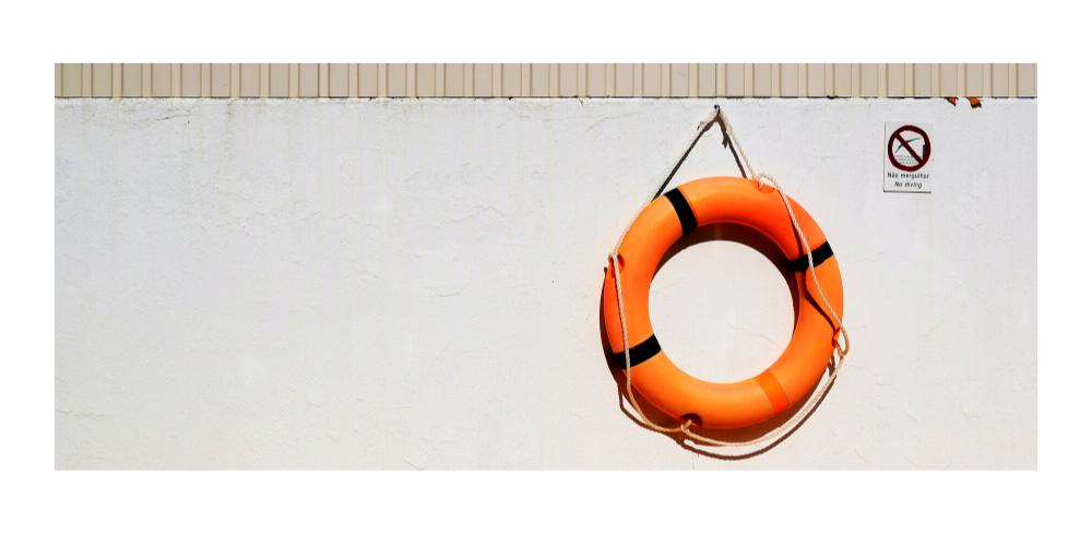 orange life preserver hanging on wall
